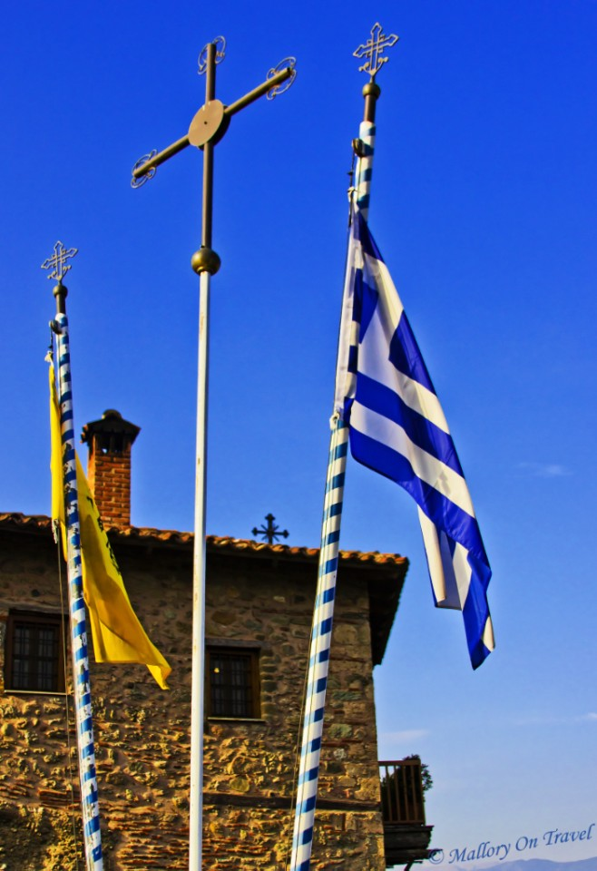 The national flag of Greece amongst others flying at a monastery in Meteora on Mallory on Travel, adventure, adventure travel, photography