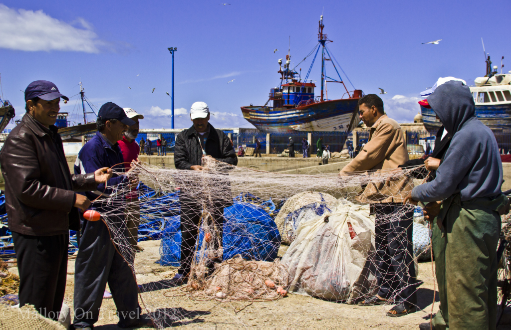 Moroccan fishermen doing net maintenance in Essaouira harbour  on Mallory on Travel, adventure, adventure travel, photography