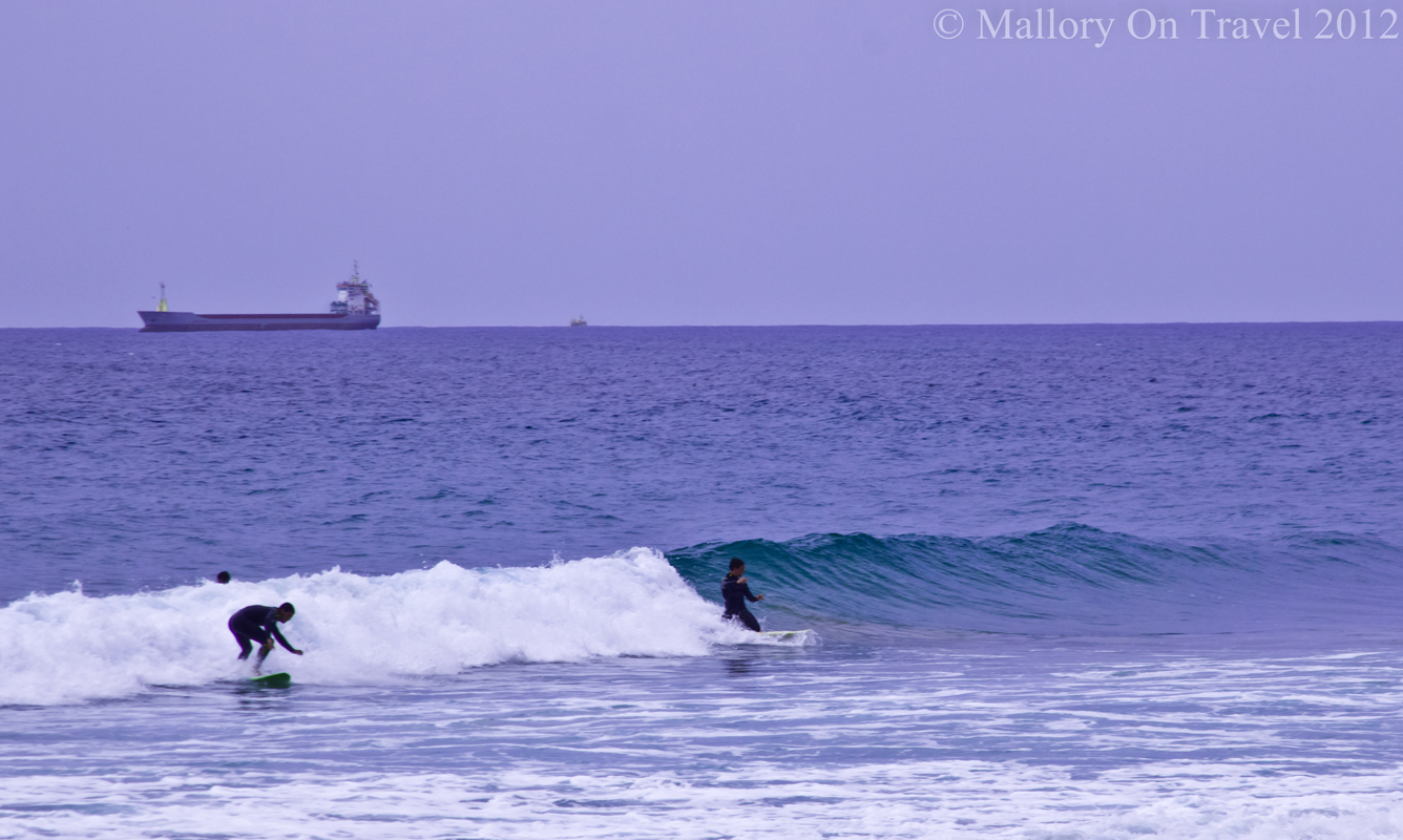 Surf's up in Tarragona, Spain with surfers and tankers on the Catalonian sea on Mallory on Travel adventure photography