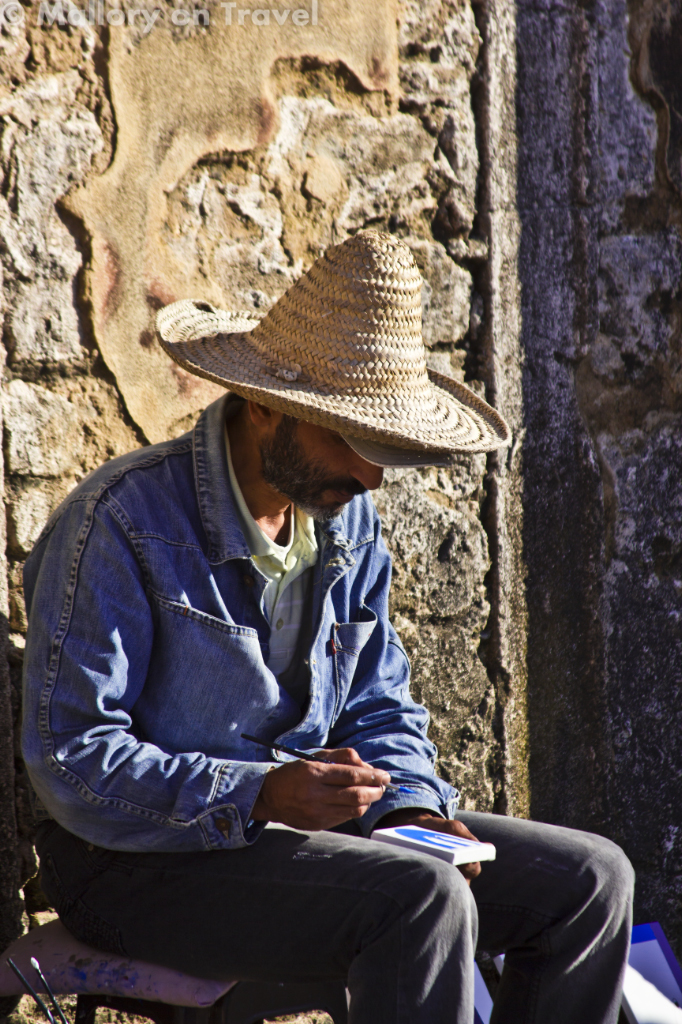 Essaouira artist at work on the fortified ramparts of the port in North African Morocco on Mallory on Travel adventure photography