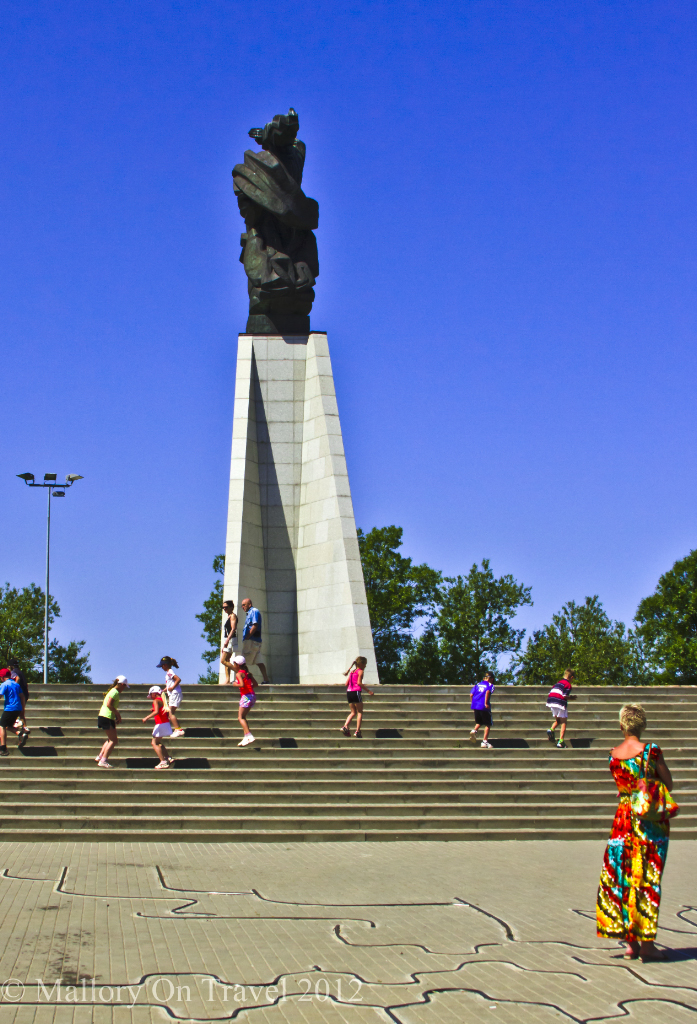 schoolchildren exercising under the 'crocodile' monument to lost sailors and fishermen on the seafront at Liepaja, in Baltic Latvia  on Mallory on Travel adventure photography