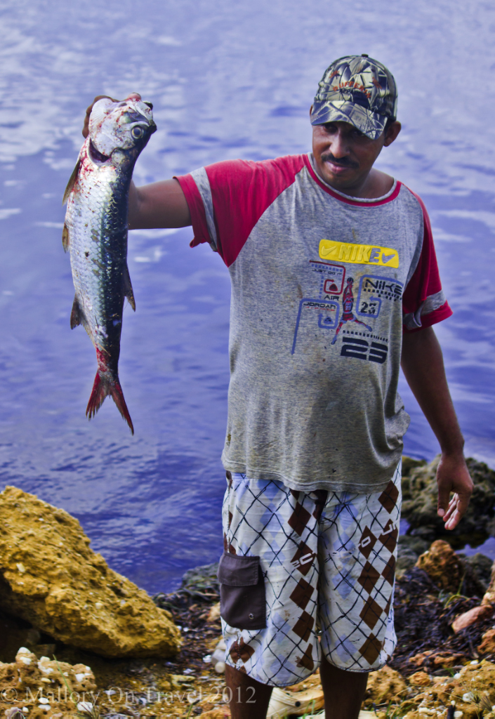 A Cuban fisherman shows off his catch near Trinidad in Cuba on Mallory on Travel adventure photography