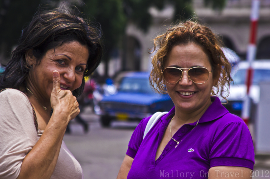 Two women happy now they've had their picture taken in Havana on the Caribbean island of Cuba on Mallory on Travel adventure photography