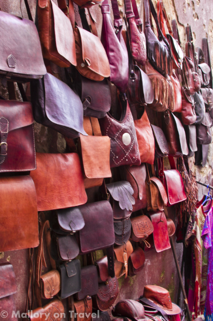 Leather bags on a wall in the souks of the medina in Essaouri, Morocco  on Mallory on Travel, adventure, adventure travel, photography Iain_Mallory_070655-1