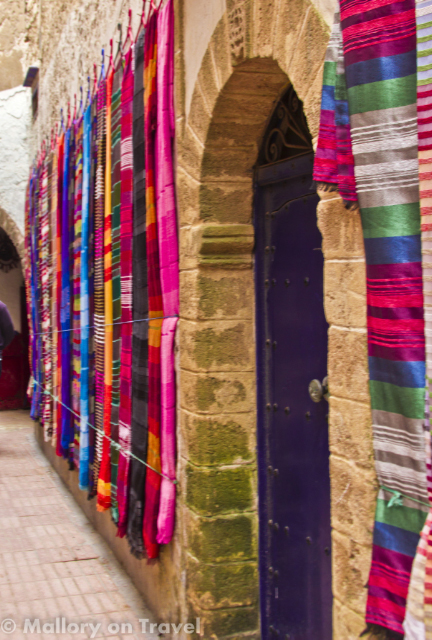 Hanging fabrics on a wall in the souks of the medina in Essaouri, Morocco  on Mallory on Travel, adventure, adventure travel, photography Iain_Mallory_071544-1