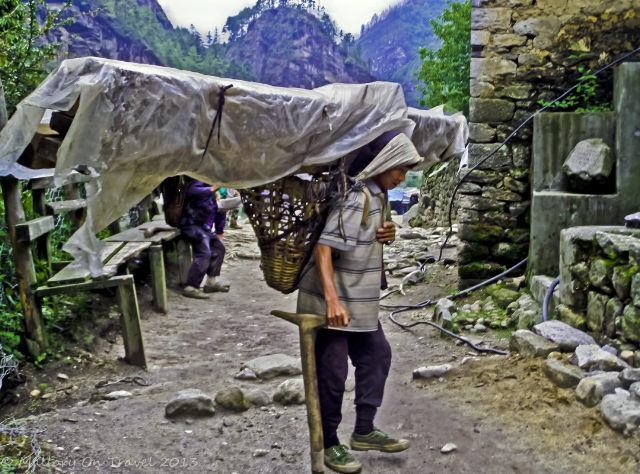 Sherpa transporting a heavy load on the Everest Base Camp trail, treks to Nepal in the Himalaya on Mallory on Travel, adventure, adventure travel, photography