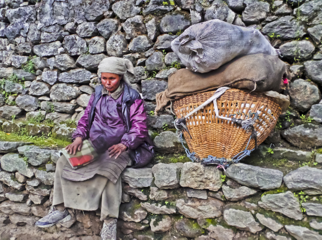 Treks to Nepal; A Sherpa woman resting with her heavy load around the Himalaya on Mallory on Travel, adventure, adventure travel, photography