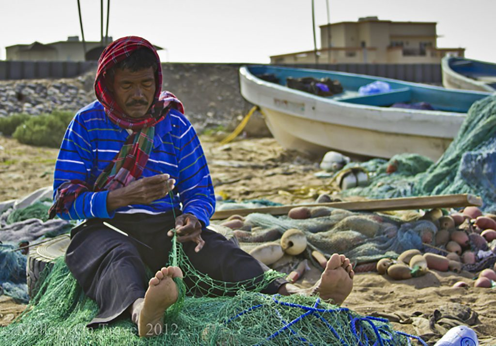 People photography; Portrait fisherman repairing his nets on the beach in Seeb, in Muscat, Oman on Mallory on Travel adventure, adventure travel, photography Iain Mallory -105 oman_fisherman