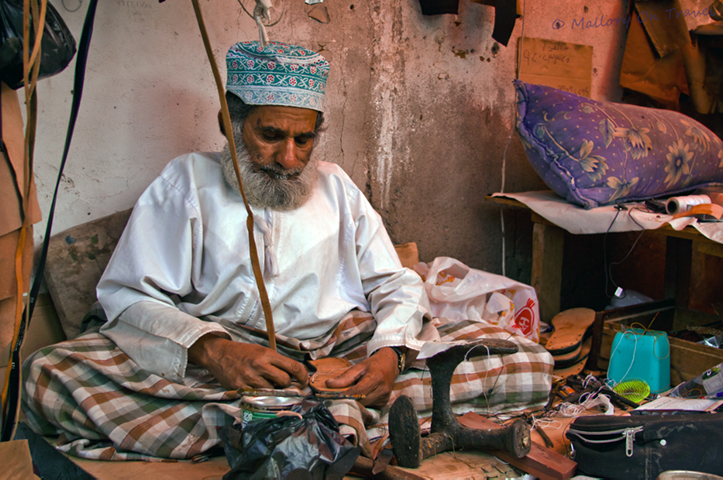 People photography; Omani shoemaker in the souk at Seeb, near Muscat, Oman on Mallory on Travel adventure, adventure travel, photography Iain Mallory -153 omani_shoemaker