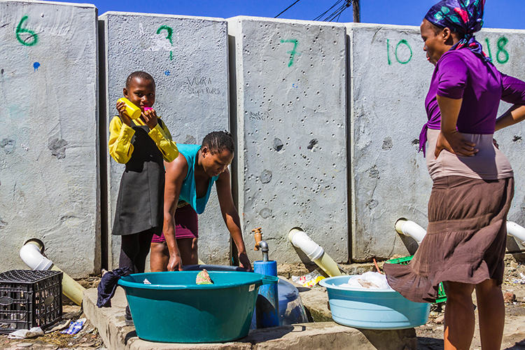 Women doing laundry in in the township of Masiphumelele  near Cape Town, South Africa on Mallory on Travel adventure, adventure travel, photography Iain Mallory-300-16 laundry_women