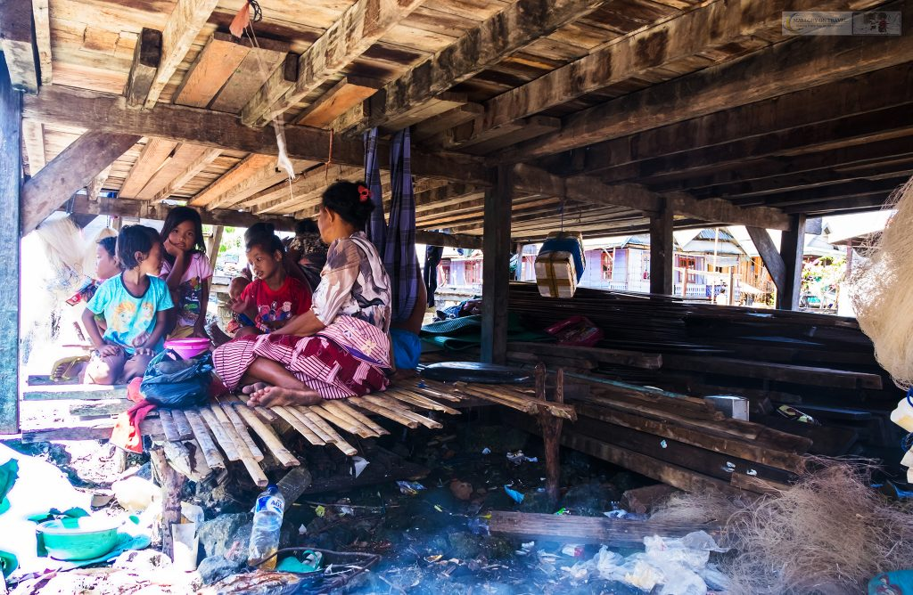 A Bajo, 'Sea Gypsies' family cooking lunch of grilled fish under the stilted houses of their Pulau Hoga village in Wakatobi, Sulawesi in Indonesia on Mallory on Travel adventure travel, photography, travel iain-mallory_indo1586