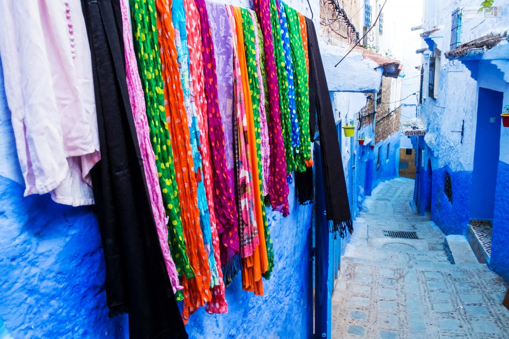 Colourful fabrics on the blue streets of Chefchaouen medina in the Blue City in the Rif Mountains of northern Morocco, north Africa on Mallory on Travel adventure travel, photography, travel Iain Mallory_Morocco 005