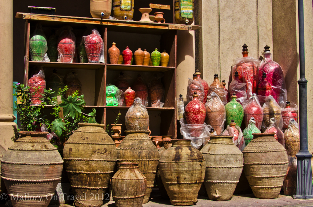 Haggling for pottery at a souk in Nizwa, Oman on Mallory on Travel adventure, photography