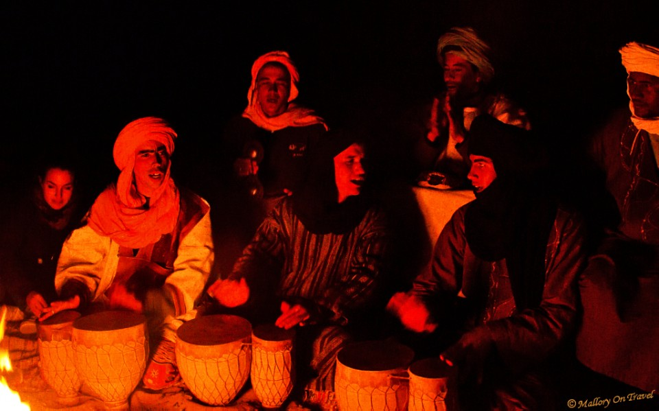Berbers enjoying some percussive music and singing in the Sahara desert of Morocco  on Mallory on Travel, adventure, photography
