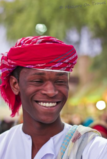 A happy, smile from a man in the Sultanate of Oman at the Muscat Festival on Mallory on Travel adventure, photography iain-mallory-307