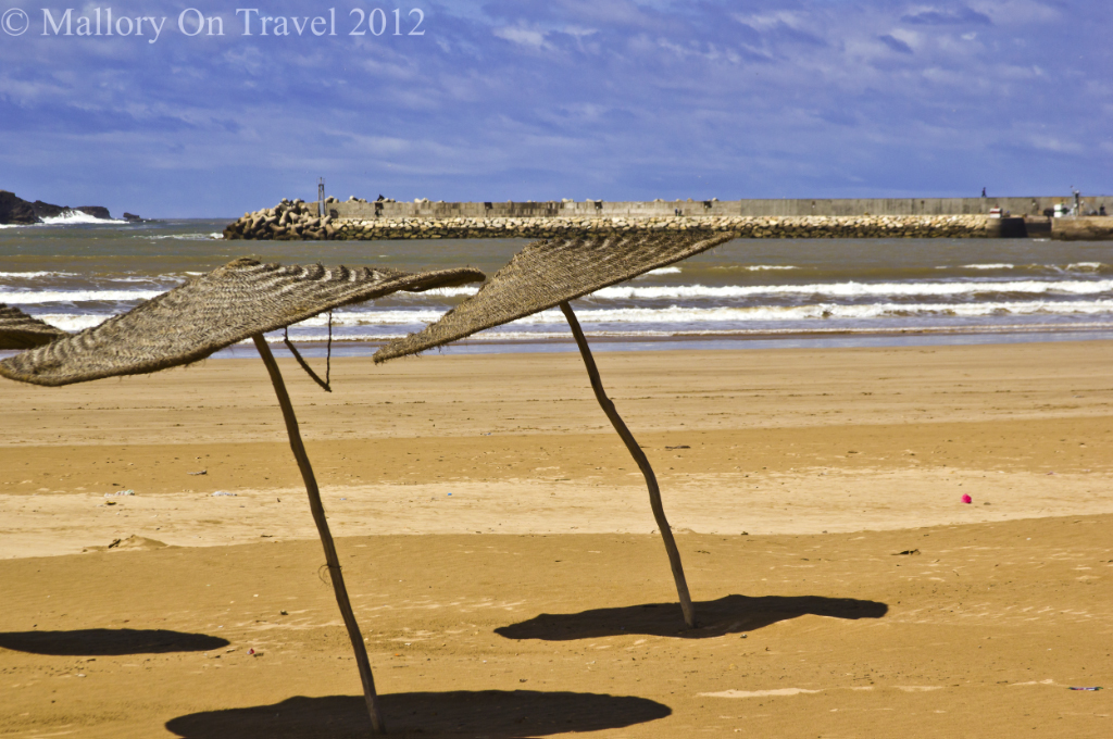 Windswept sunshades on the beach at Essaouira in Morocco on Mallory on Travel adventure photography