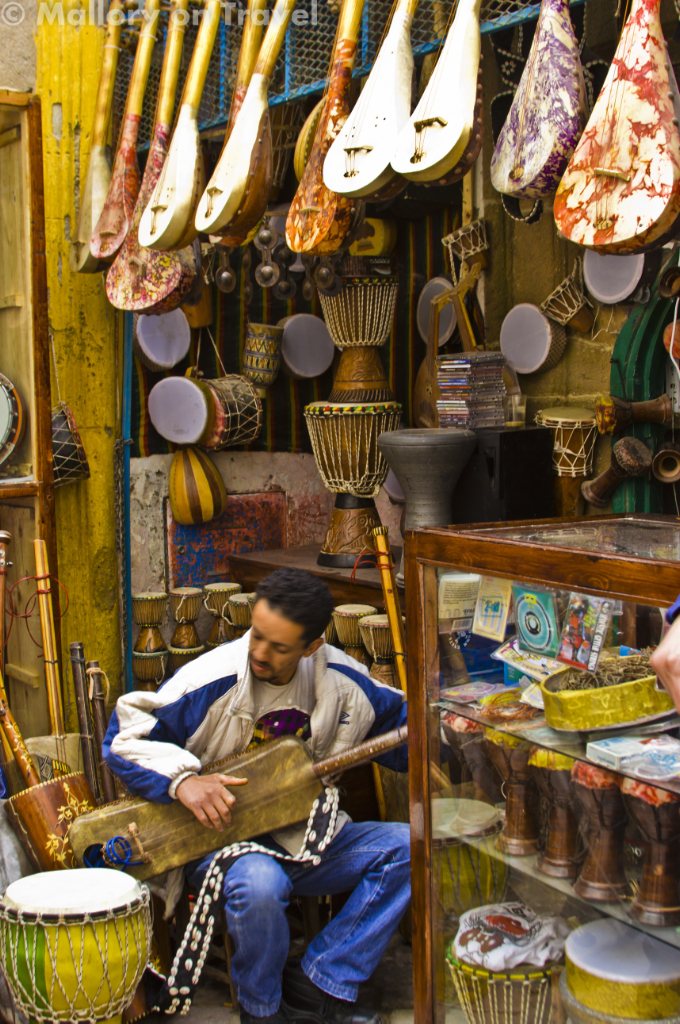 Traditional Gnawa musician playing a gimbri in the median of Essaouira, Morocco on Mallory on Travel adventure photography