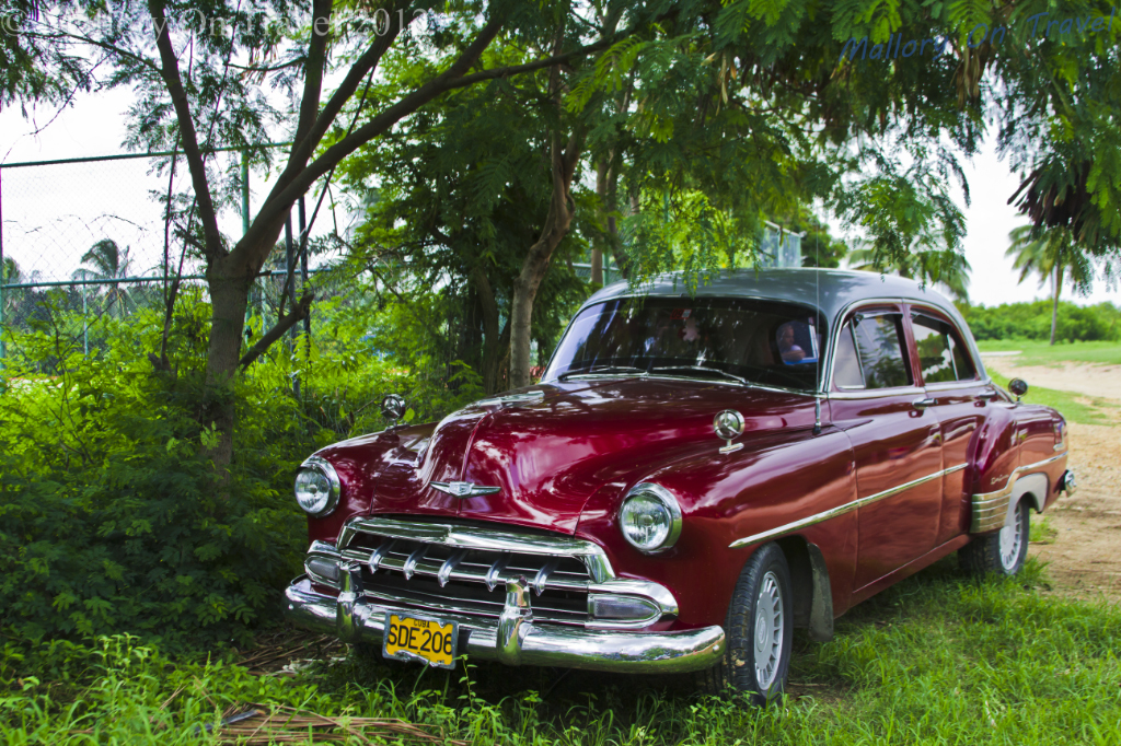 Classic cars on the Caribbean Ancon Peninsula near Trinidad, Cuba on Mallory on Travel adventure photography