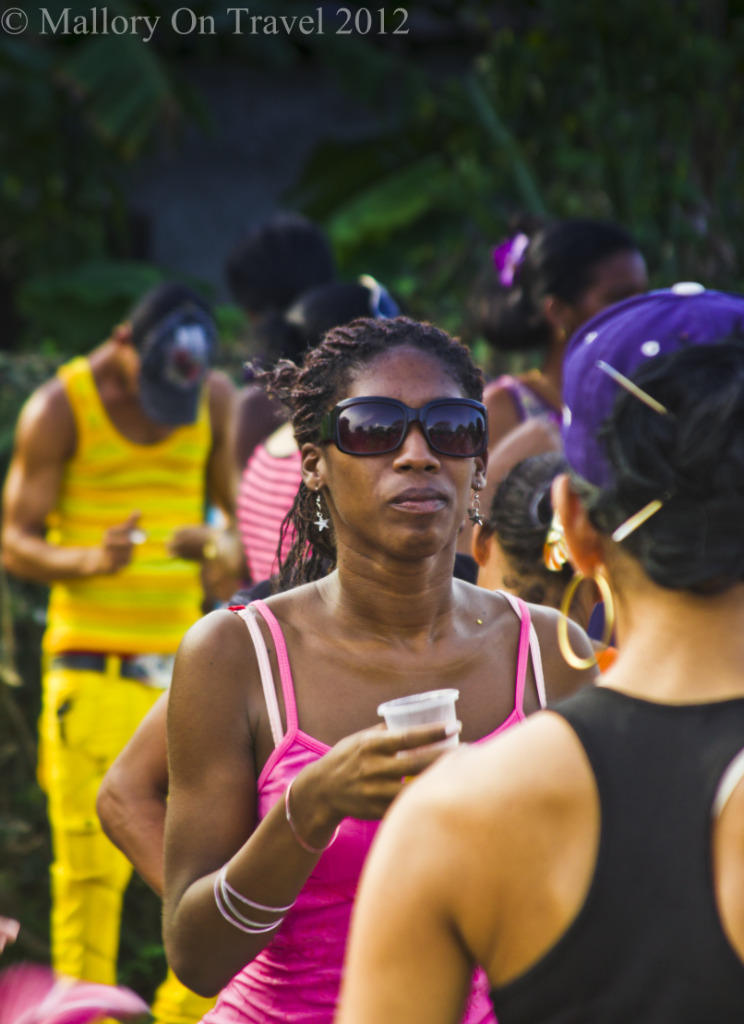 Black woman partying at the Camaguey Carnival on the island of Cuba in the Caribbean on Mallory on Travel adventure photography