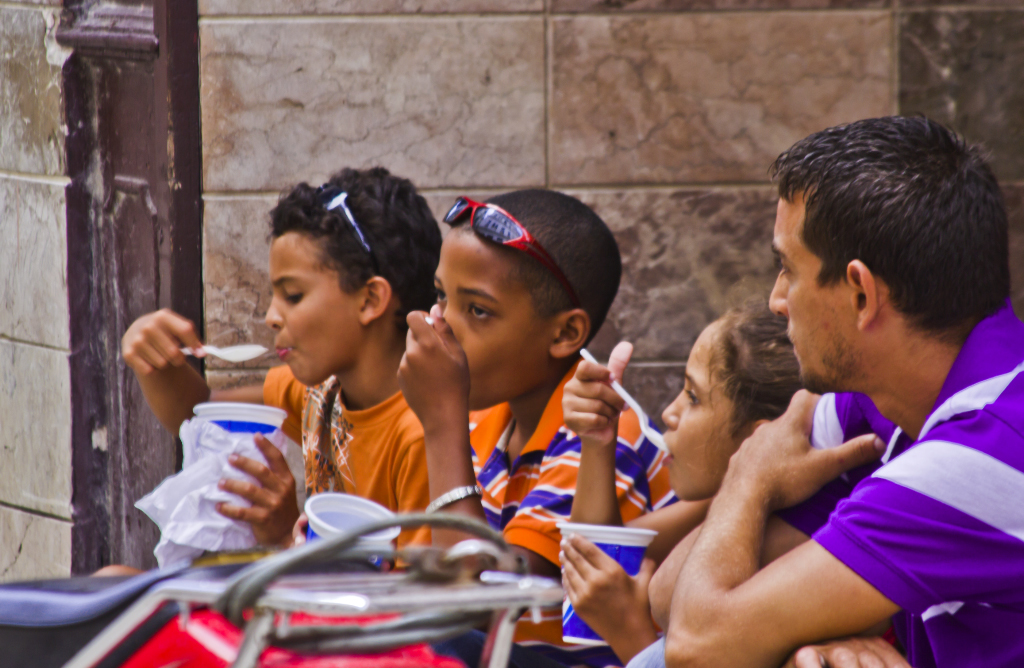 Children  enjoying ice cream in Havana on the island of Cuba in the Caribbean on Mallory on Travel adventure photography
