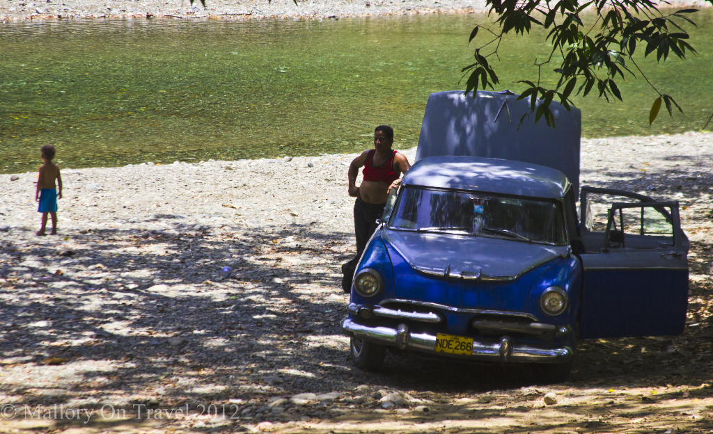 A classic car down by the river in Baracoa on the Caribbean island of Cuba on Mallory on Travel adventure photography