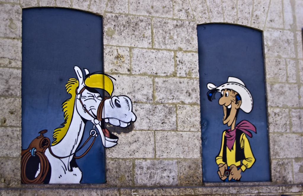 Laughing horse and cowboy comic mural in Angoulême in the Poitou-Charentes region of France on Mallory on Travel adventure photography