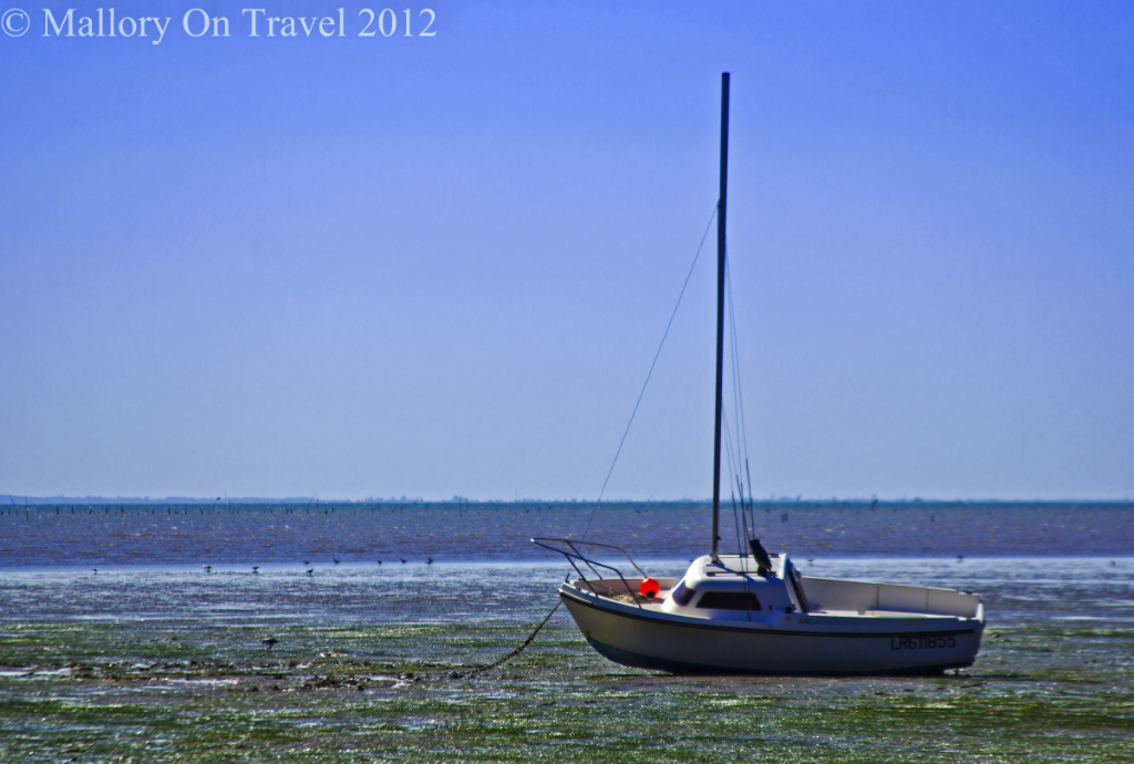A stranded boat at low tide on  Île-d'Aix in the Charente-Maritime region of France on Mallory on Travel adventure photography
