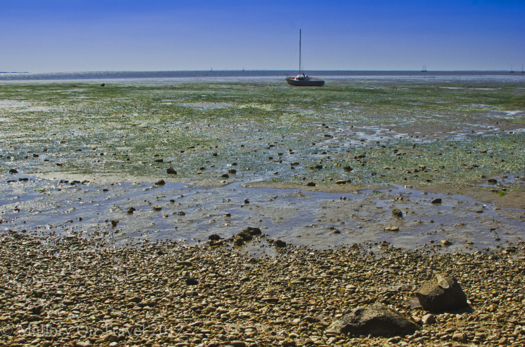 A small stranded fishing boat at low tide on Île-d'Aix in the Poitou-Charentes region of France on Mallory on Travel adventure photography