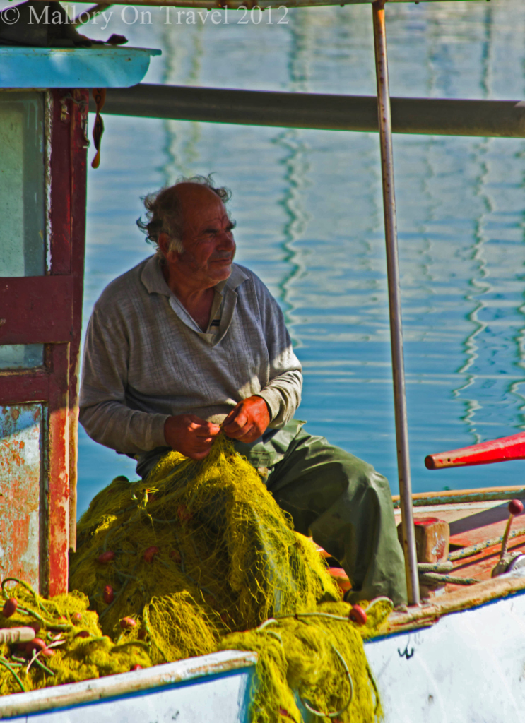 A fisherman in the harbour in Heraklion, on the island of Crete, Greece on Mallory on Travel adventure photography