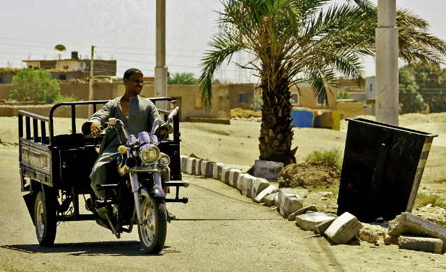 A tuk-tuk delivery rider near Luxor and the Valley of the Kings in Egypt on Mallory on Travel, adventure, adventure travel, photography egyptiantuktuk