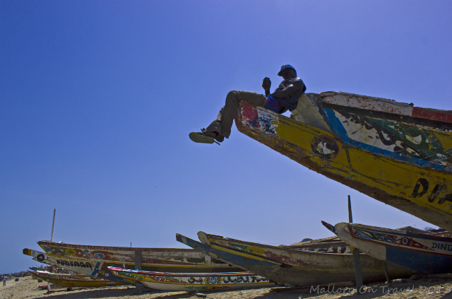 Perched high on a pirogue at Tanji market in The Gambia, Africa on Mallory on Travel, adventure, adventure travel, photography Iain Mallory-300-27