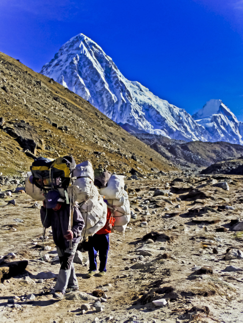 Treks to Nepal; Sherpa porters in the shadow of Pumori in the high Himalaya adventure, adventure travel, photography on Mallory on Travel