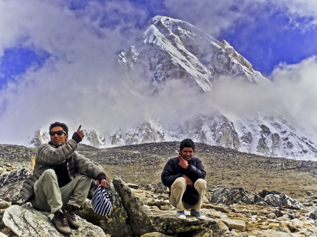 Treks to Nepal; Sherpa guides in the shadow of Pumori in the high Himalaya, Sherpa porters in the shadow of Pumori in the high Himalaya, Nepal